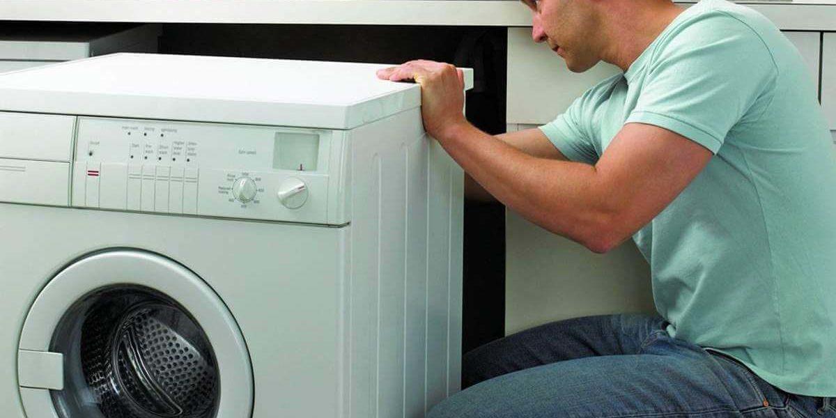 Мастер ремонтирует стиральную машину