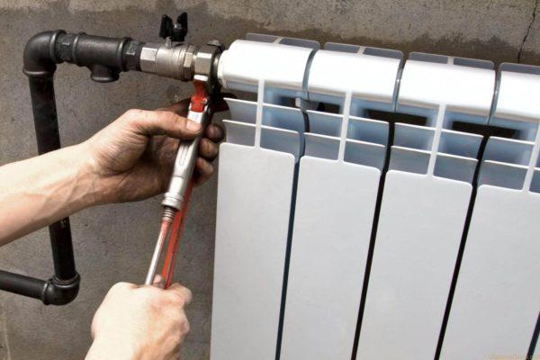 Сантехник устанавливает радиатор батареи